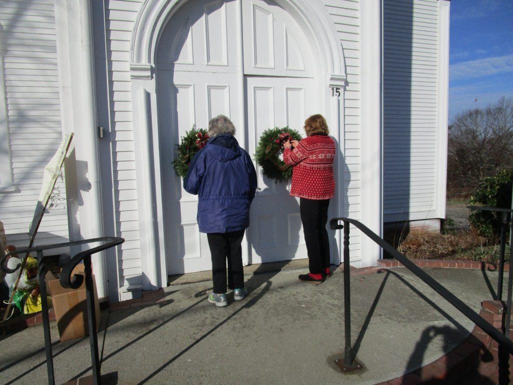 Two women hanging wreaths on the church door